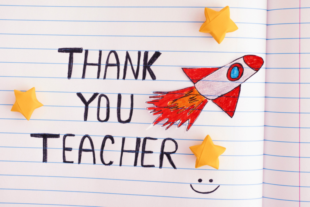 Thank you teacher writtern in child's handwriting in a notebook with lined paper. Has a hand drawn rocket in red and white and yellow stars on it